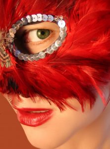 A woman in a red feathered mask showing only her eye and red lips