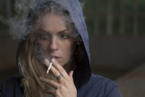A woman in a hoodie smoking a cigarette